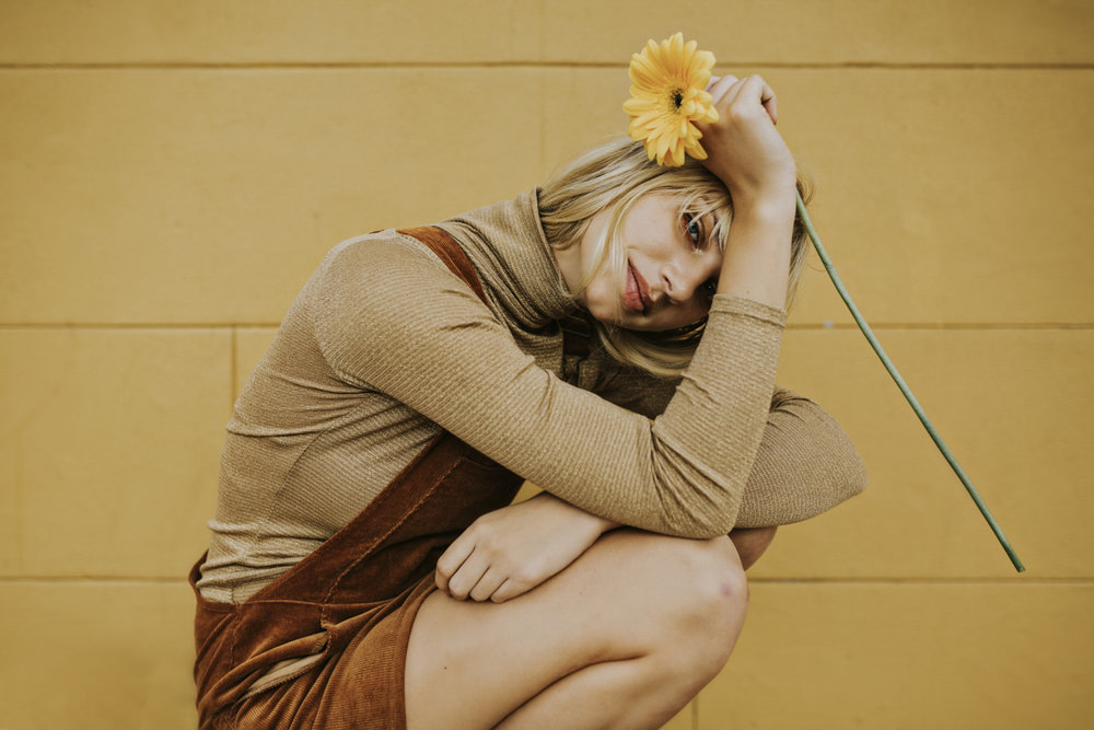 Beautiful model poses with yellow flower in front of yellow wall