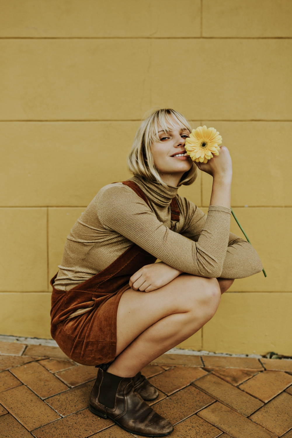Iris Hall poses with yellow flower in front of colourful wall du