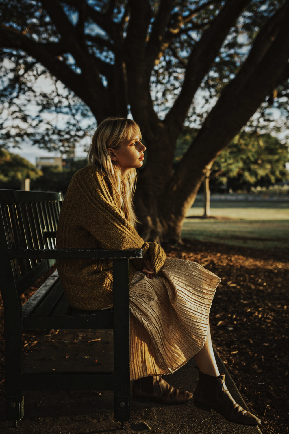 Blonde model gazes at sunset on a park bench during beautiful ph