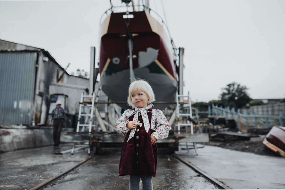 Young girl with funny expression stands in front of boat at dock