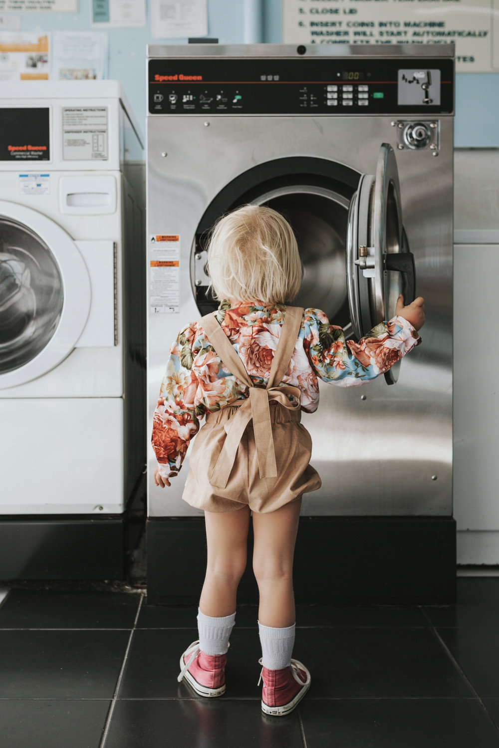 Young girl with bed hair looks into washing machine.