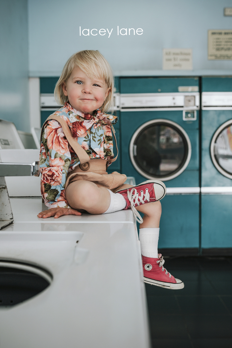Blonde girl sits on washing machine in laundromat with cute outf