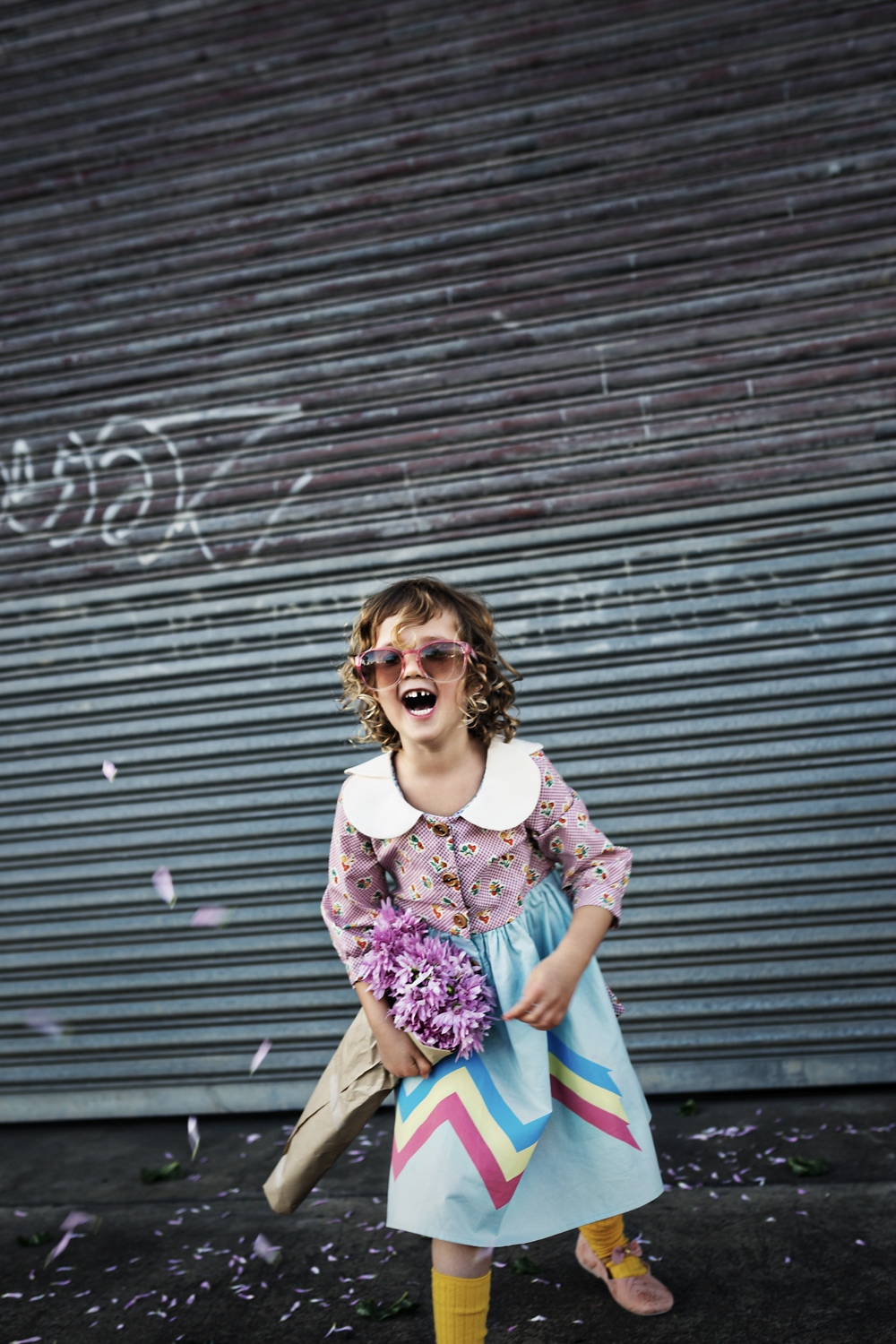 Girl with curls laughs during fun photo shoot.