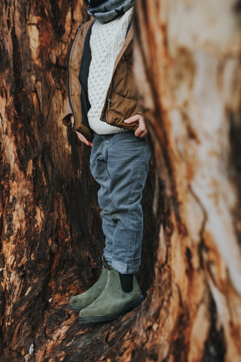 Young boy stands in a tree with dirty knees wearing Blundstone boots and winter clothing.