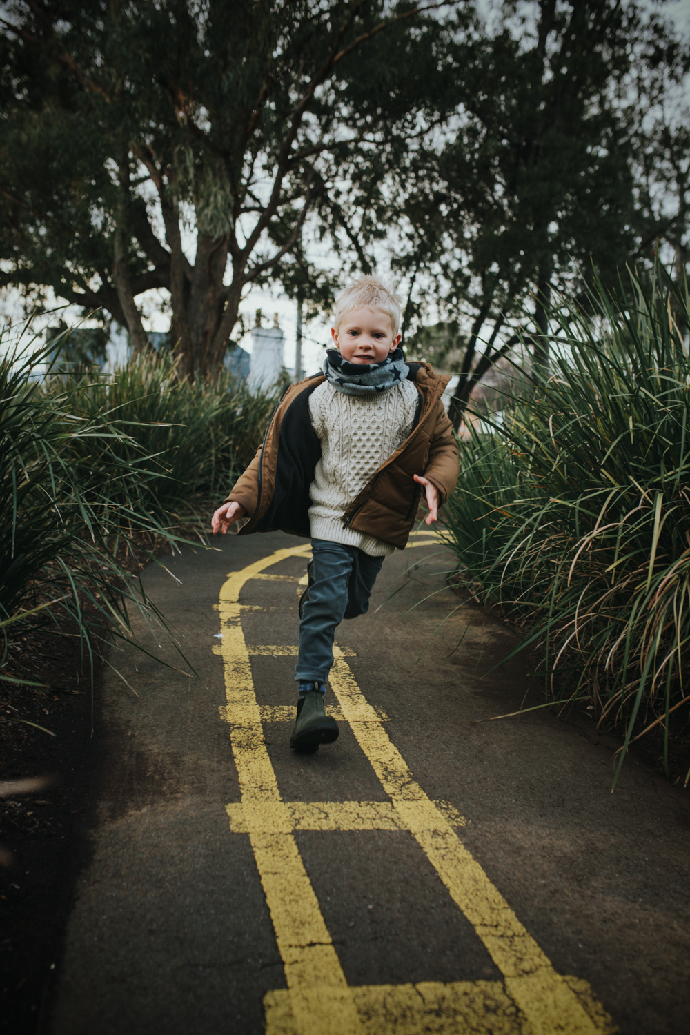 Young blonde boy runs through park wearing Blundstone boots in Hobart Tasmania.