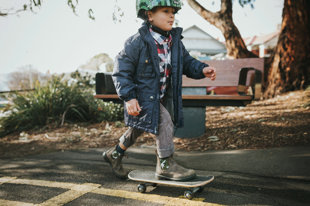 Young boy skateboards wearing Blundstone boots in a playground.