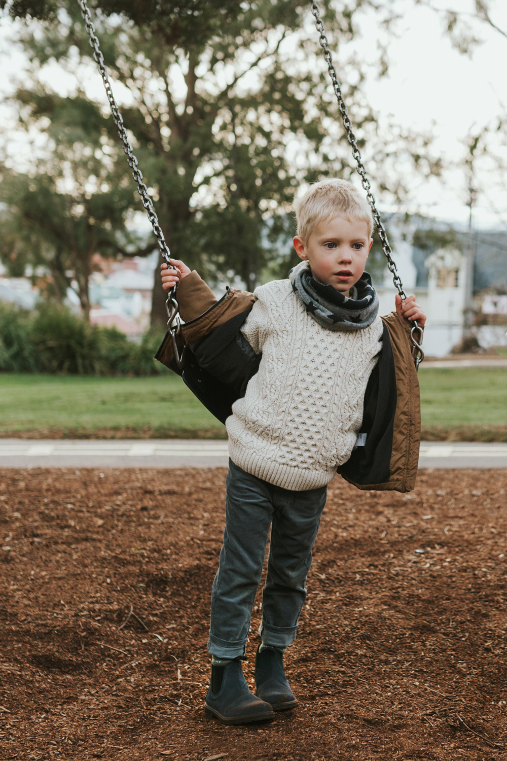 Young boy stands by a swing wearing Blundstone boots in Tasmania.