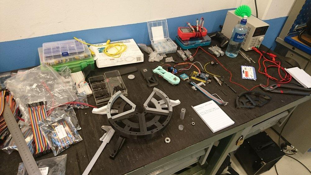 Her ser man arbeidsbenken vår med forskjellige prototyp-deler strødd rundt, samt starten på basen til armen som den skal stå på.
