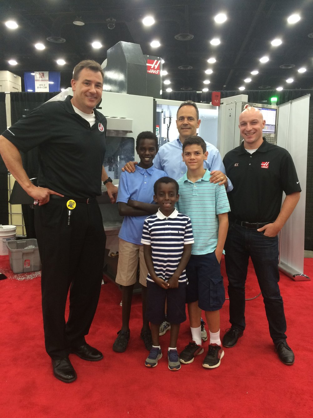 The photo was taken on Sunday at the 2017 NSRA (National Street Rod Association) Nationals event in Louisville, Kentucky. Featured in the photo is Kentucky Governor Matt Bevin with his 3 boys. Also shown are Phil Haming, HFO Midwest Sales Engineer (shown left) and Aaron Evans, HFO Midwest Application Engineer (shown right). The machine in the background is a Haas DT-2 Drill Tap Machining Center, used in high-volume production of precision parts. As you know, this machine is made by Haas Automation in their Oxnard, CA factory.