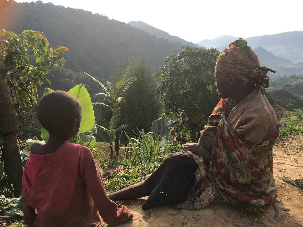 90 year old Batwa woman sits with her grandson on the rain forest edge as she remembers and longs to go home.