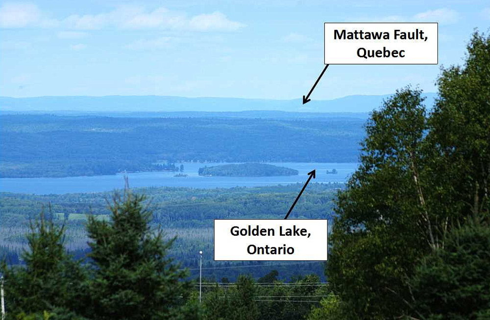 Figure 13: Looking northerly across the Ottawa - Bonnechere Graben from Foymount, on top of the Opeongo Mountains, across the Petawawa Fault (hidden by the trees in the front), across Golden Lake within the valley of the Ottawa - Bonnechere Graben, to the abrupt cliffs of the Gatineau Hills, which show the location of the Mattawa Fault. Photo by Andy Fyon, August 27, 2016.