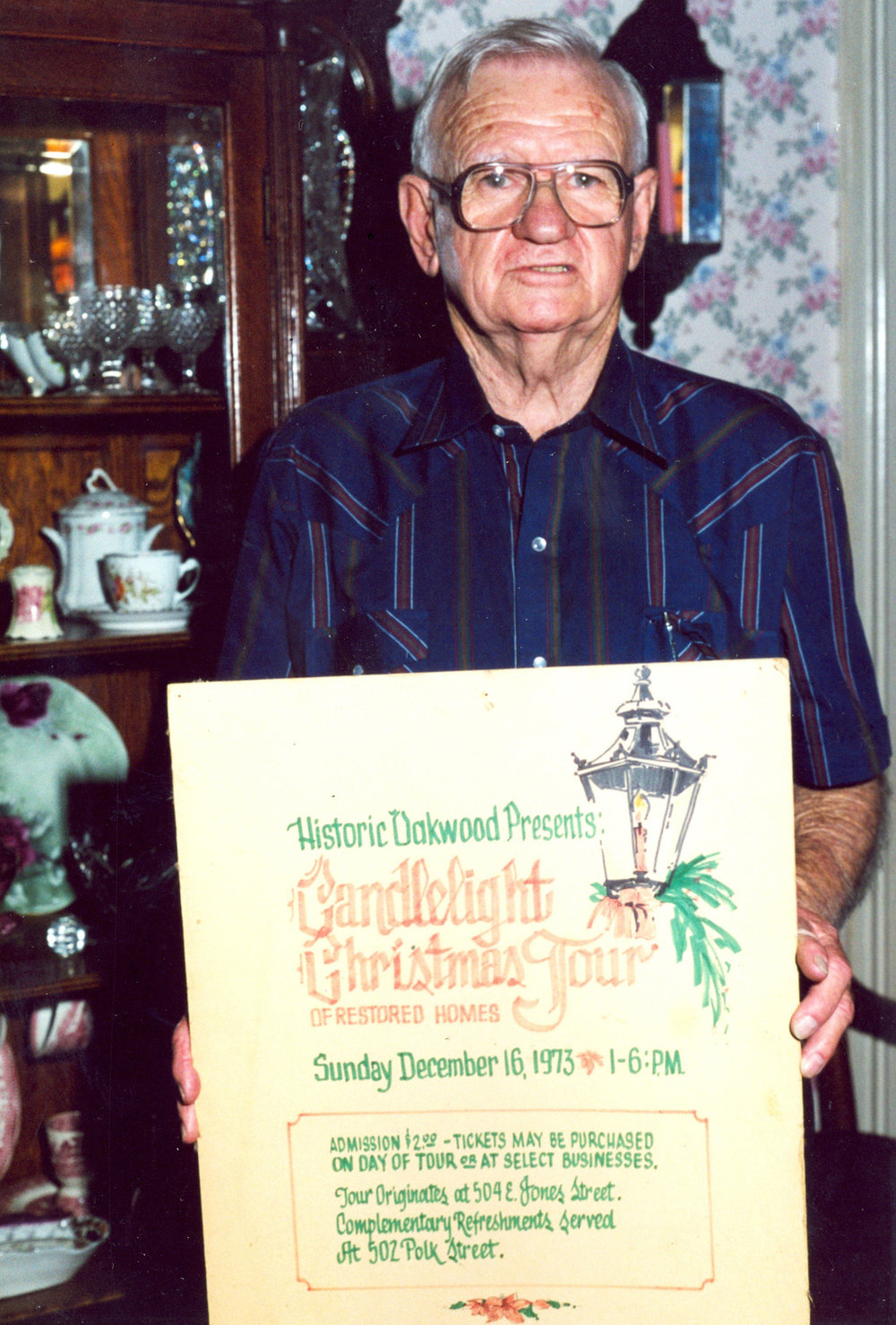 Bill Hutchins holding an original first Candlelight Tour poster