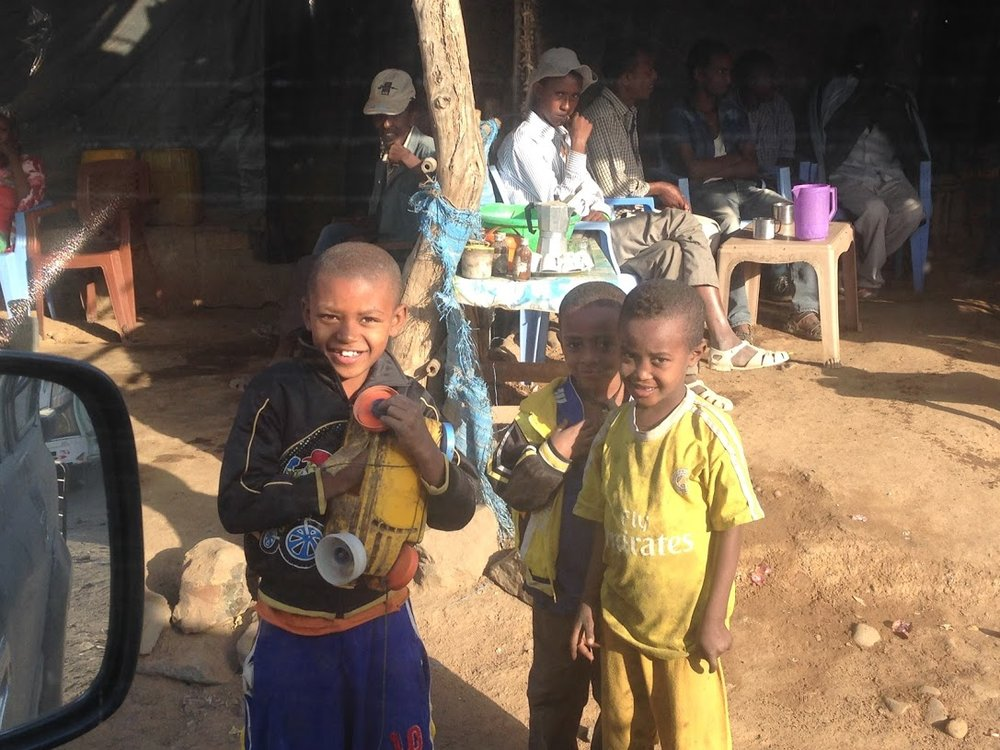 Three children from the village Aykel, pictured with their toy car made from plastic cans and lids.