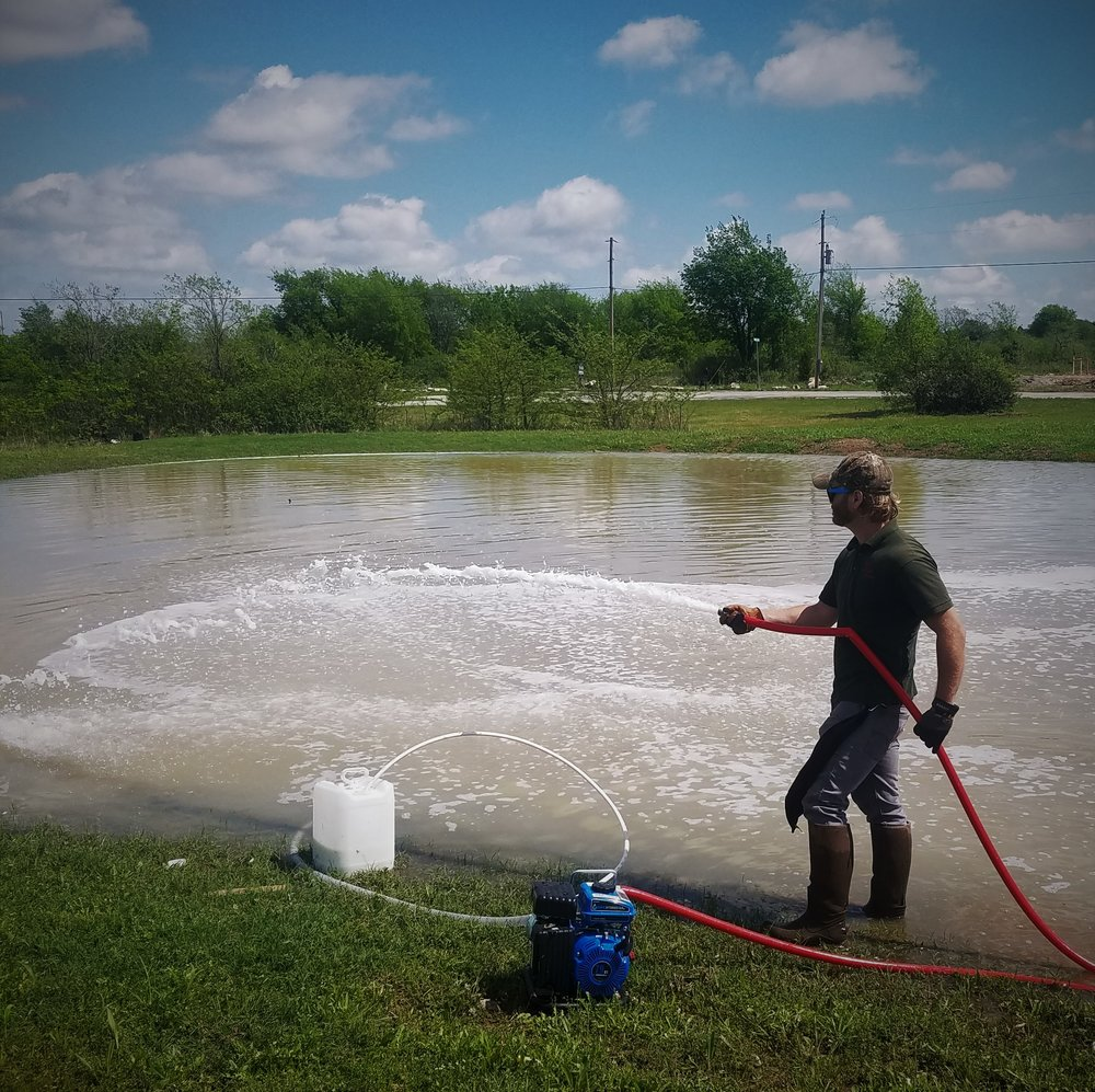 Pond Sealing - It seems almost everyone either has a pond that leaks...or knows someone that does! Oklahoma has many different soil types that seep, plants and animals that make holes, and older ponds with dam issues. We use a liquid polymer sealant that will find leaks and expand to fill them! There is even a granular formulation that can be used to prevent leaks in newly constructed, dry ponds. The days of applying heavy, expensive clay, that never seems to work, are over!Pictured here is Biologist, Jarryd Robison, applying liquid sealant to a pond near Collinsville.