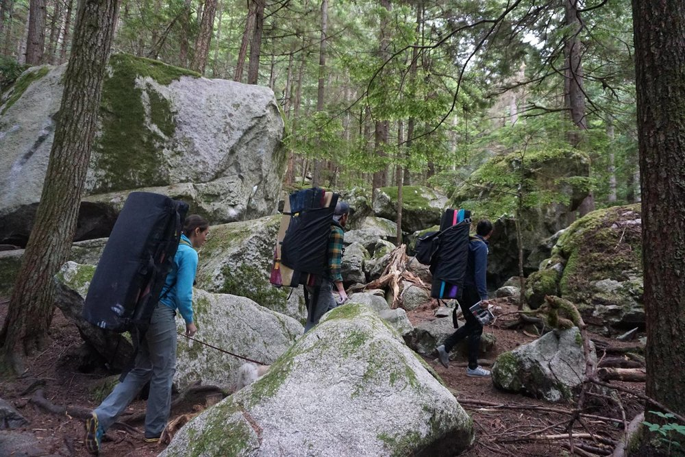 Boulderers carry crash pads on their backs through the boulder field in Squamish, BC.