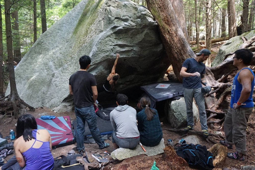 A group of climbers, mostly strangers, gathers together to cheer each other on as they take turns attempting a boulder problem.
