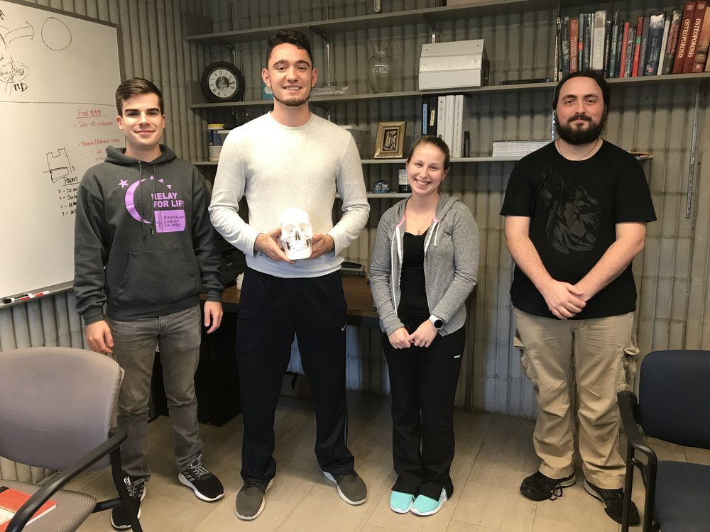 - CUTTING JIG TEAM (2017-2018)Our team is 3D printing and building an adjustable device that integrates with a band saw, and that can be used to cut large, irregular shaped bone specimens needed for various types of research projects. (From left to right: Alec Riendeau, Jake Aaronson, Eliza Marks, Andrew Ahrens)
