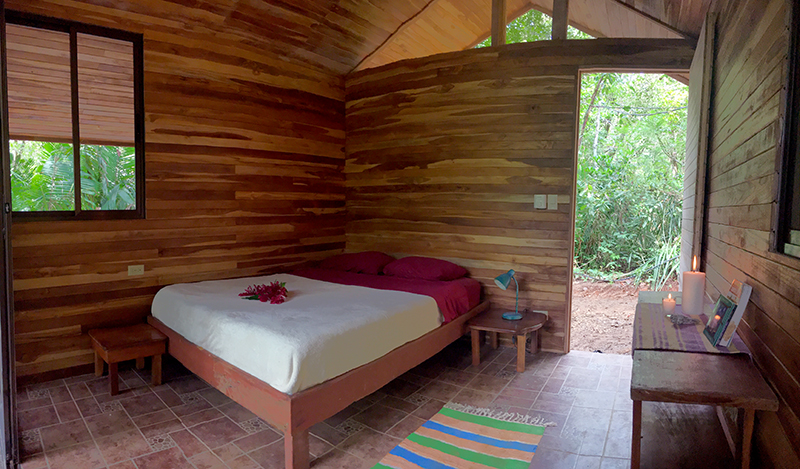 These open-air, screened in bungalows are about 2 minutes walking distance from the village center. The bungalows merge comfort and organic qualities by providing a completely screened in option built from wood in the pristine PachaMama forest. Furnished with a standard queen-size bed, all bungalows are ideal for up to two adults. Sliding screen doors separate the main space from the balcony to make this accommodation completely bug-proof. Ceramic floors, wooden walls and a covered balcony give a very cozy feeling overlooking the forest. Standard bungalows measure 14 sq meters and each have private hot showers and are located in the vicinity of shared compost toilets.   Bungalow Package:  Early Bird $1020 / Regular $1050   Shared Bungalow:  Early Bird $1830 / Regular $1890