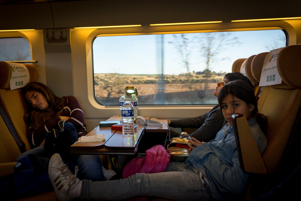 camila, carlos and lorena ride the train from sevilla back to madrid in spain