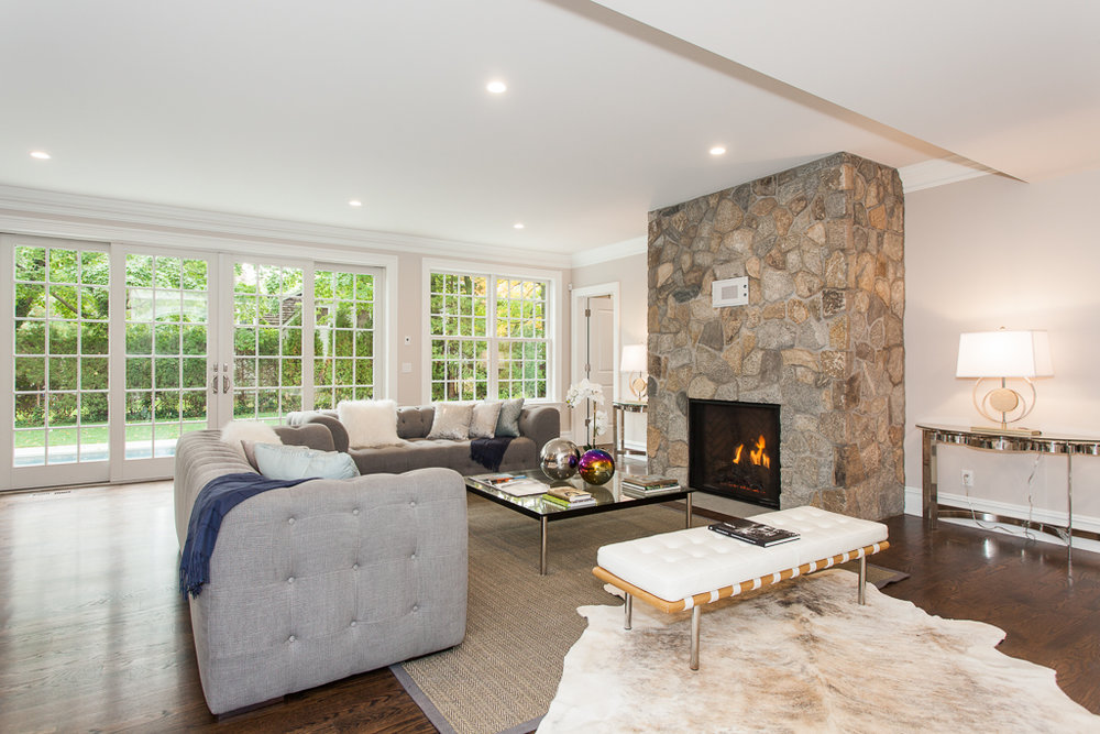 FAMILY ROOM |  Expansive & Bright Family Room   is open to the kitchen and features walls of glass, double french doors to the pool and property and a stone-surround gas burning fireplace.