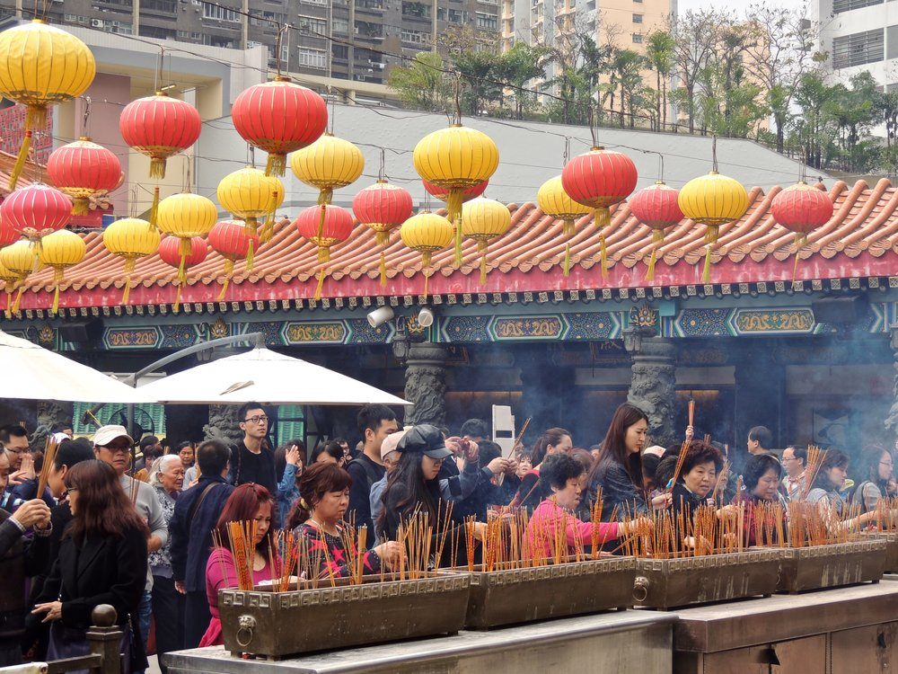 People worshipping and burning incense.