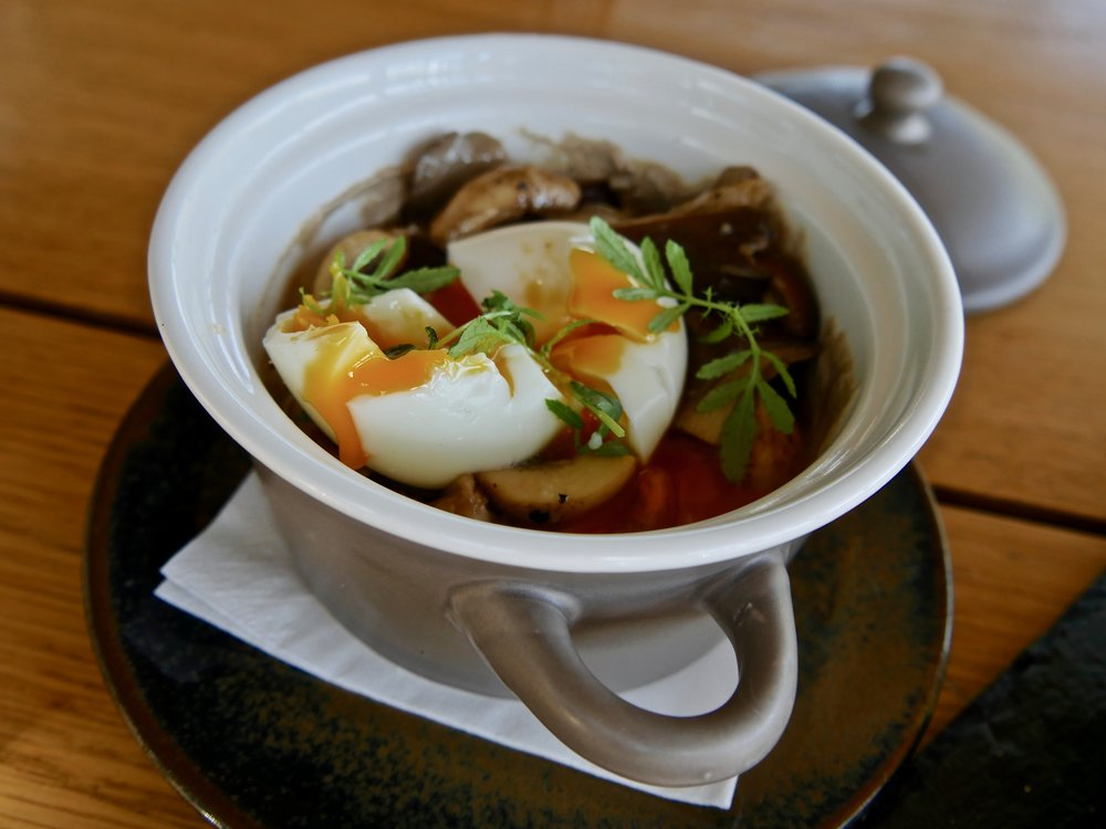 3 textures of mushrooms with a poached egg and fresh local herbs.