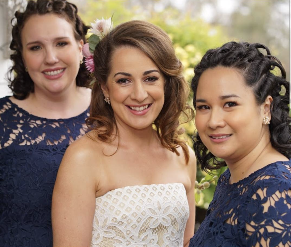 A bride in white with her bridesmaids.