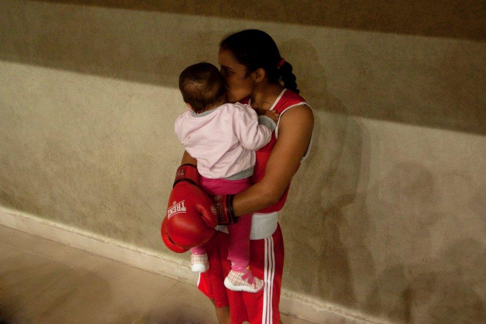 Hug, Sport hall, Ranchi, Jharkhand, India, 2013 © Mélanie Dornier Meena Kumari, femme policière et boxeuse, tient sa fille dans ses bras avant son entrée sur le ring. Il s'agit de son premier combat depuis son accouchement.