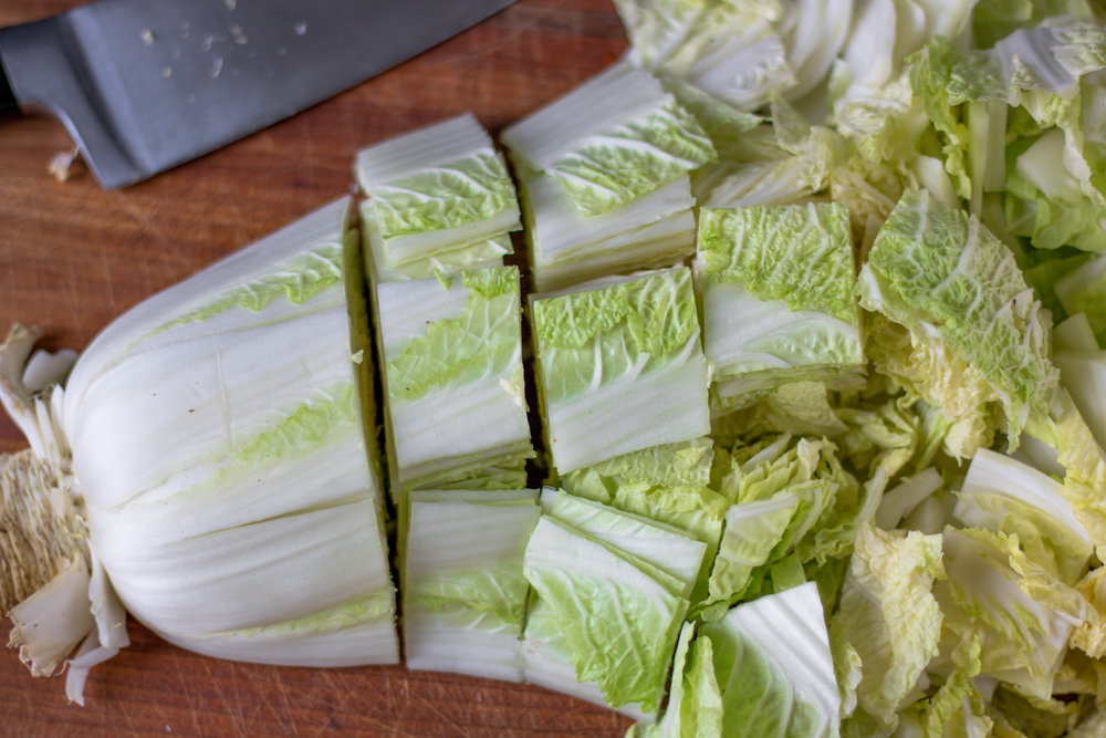 "Slice the cabbage lengthwise into thirds. Then, slice the opposite way into large 2"" x 2"" pieces."