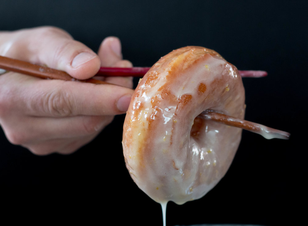 "We keep the glaze room temp. Dipping the fresh fried donuts into the glaze almost ""wakes"" the glaze back up so that it can coat all of the fresh fried dough! Roll those suckers all around in the glaze, being sure to coat all the sides. We used chopsticks to make it easier to handle."