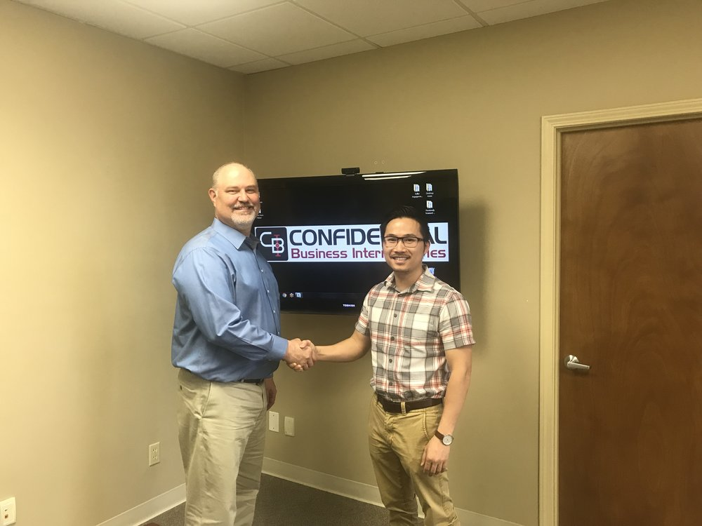 Dr. Scott Taylor (left) shakes hands with new owner, Dr. Isaac Le.