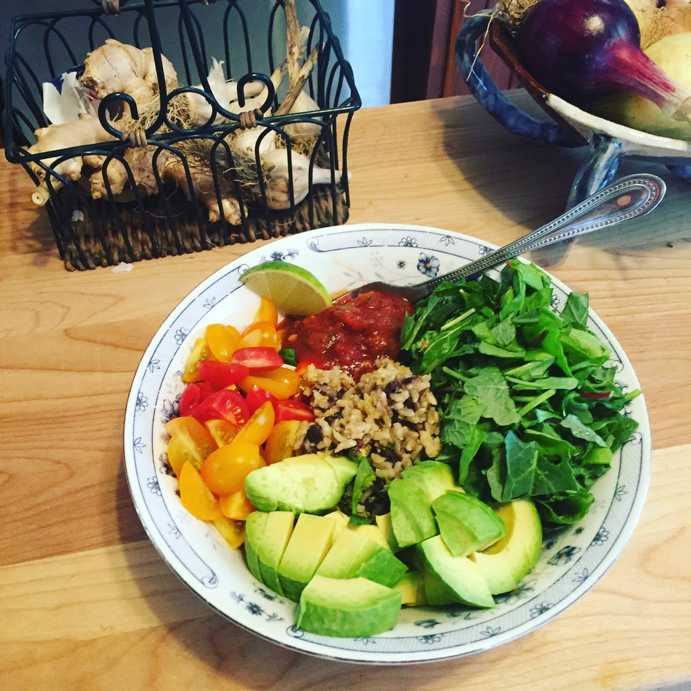 Plant based whole food meal with black beans and rice, salsa, avocado, tomatoes, and fresh spinach.