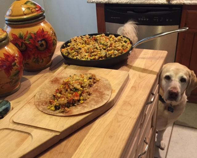 Sweet potato black bean burritos - preparing burrito with Daisy peeking.jpg