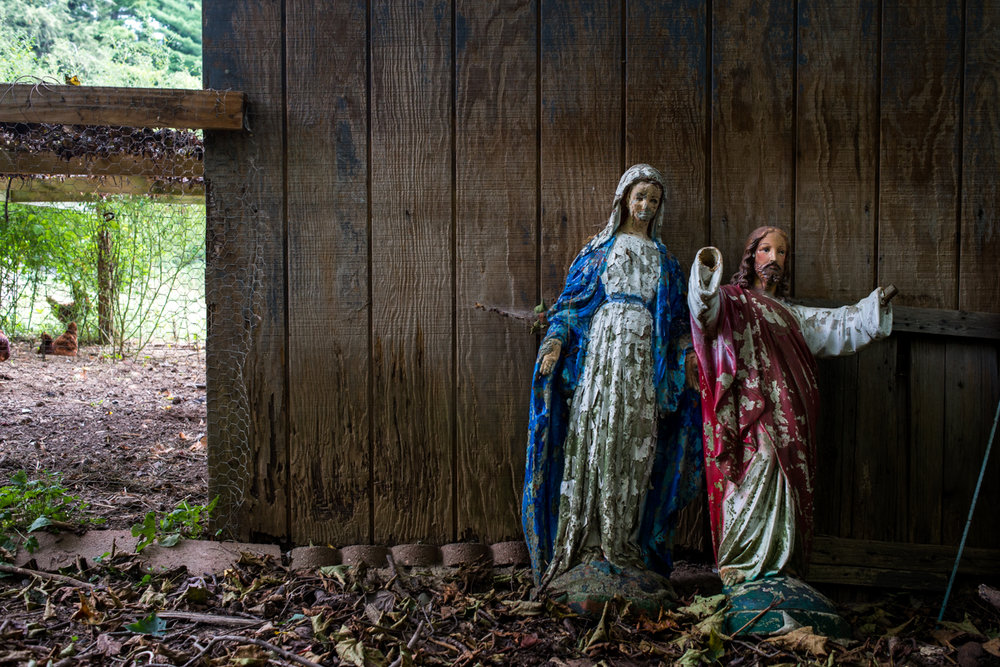 Statues of Mother Mary and Jesus, sitting behind the chicken coop after the paint began to chip and age.
