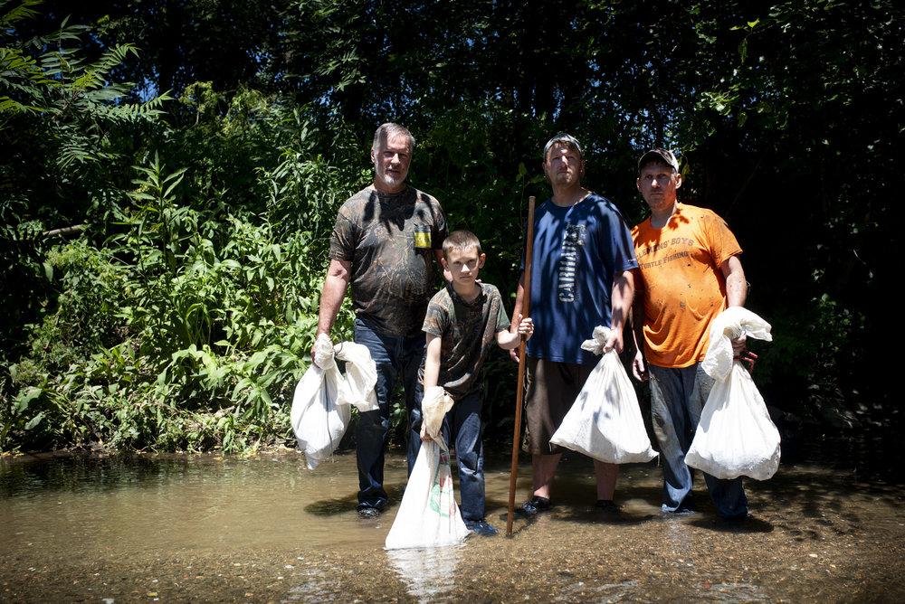 Vince, Adyn, Joey, and Joe Clemens poses for a portrait with sacks full of snapping turtles before they get out of Sewickley Creek.