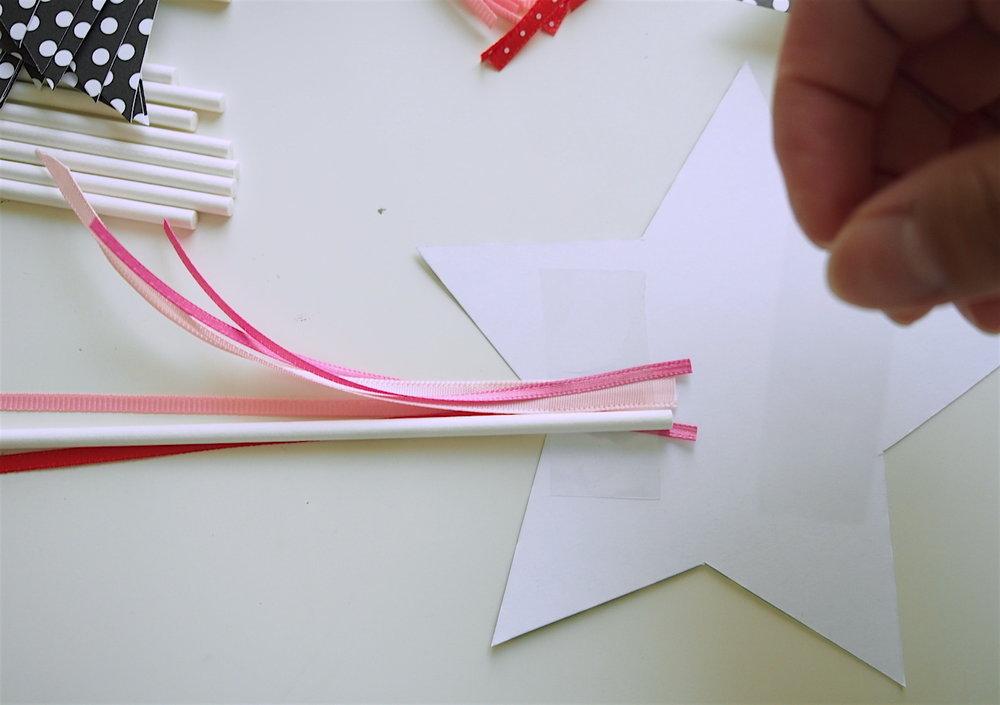 そして、内角の真上(リボンに少し重なる)にスティックを置いてテープで固定します。そうすることで、リボンとスティックが重ならず見栄えが良くなります。