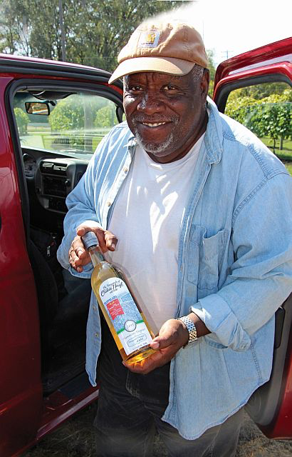 Mansfield Frazier proudly displays a 2014 bottle of his Traminette Vigonier, which came in second place at the Geauga County Fair. (Photo credit: Margaret Puskas)