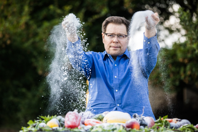 Mathematician Irakli Loladze tosses sugar over vegetables outside his home in Lincoln Nebraska, to illustrate how the sugar content of the plants we eat is increasing as a result of rising carbon dioxide levels. Loladze was the first scientist to publish research connecting rising CO2 and changes in plant quality to human nutrition. | Geoff Johnson for POLITICO