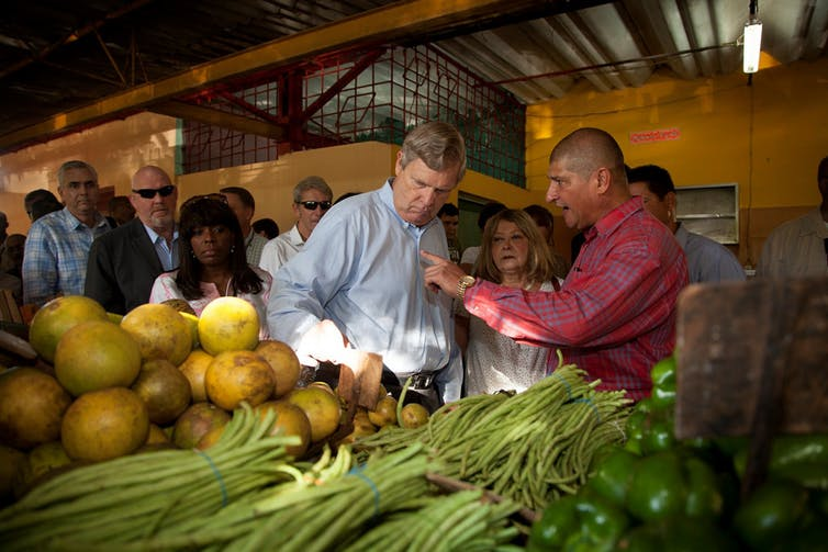 Then-Agriculture Secretary Tom Vilsack speaks with Provincial Agriculture Deputy Julio Martinez during a visit to a local farmers market in Havana, Cuba, Nov. 13, 2015. USDA/Lydia Barraza.