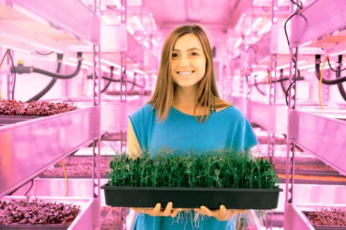 Sprouting up:  Margot Masinter holds a flat of microgreens grown inside a recycled shipping container.  Billy Surface