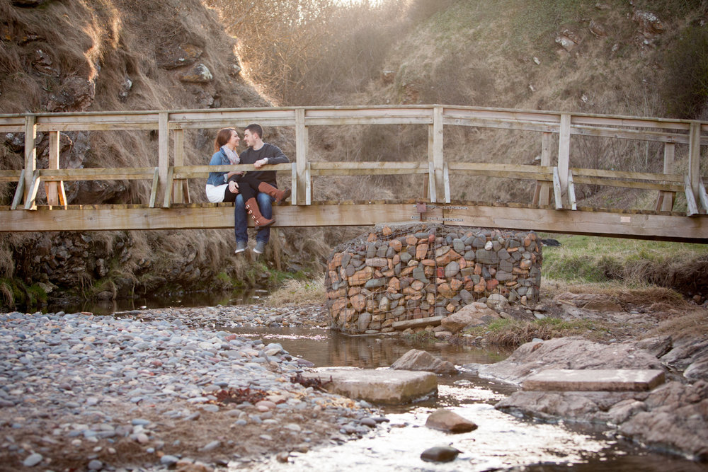 Couple on walkway bridge over small stream in Autumn