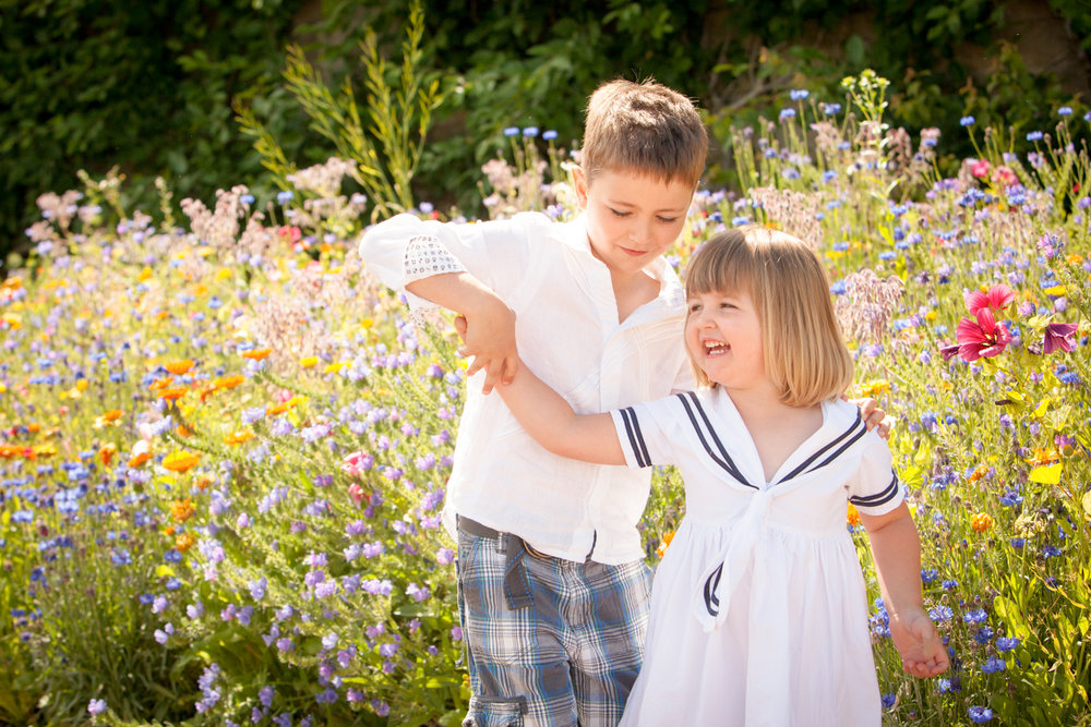 children playing together sister and brother in wild flowers