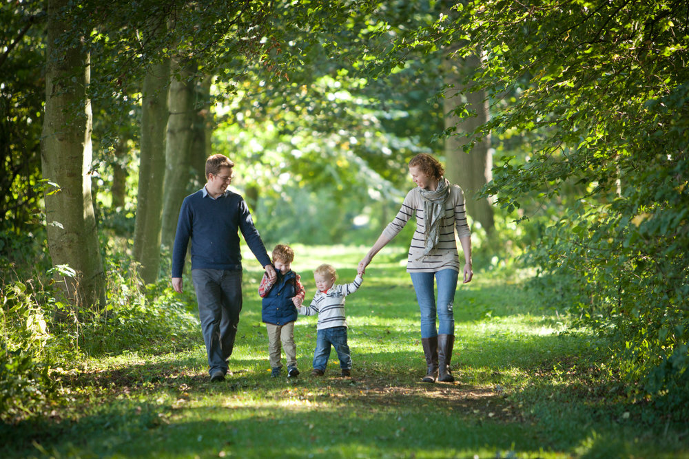 family with two boys walking in the woods with dappled sunlight behind