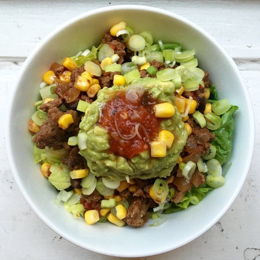 spicy beef bowl layered with greens + guacamole