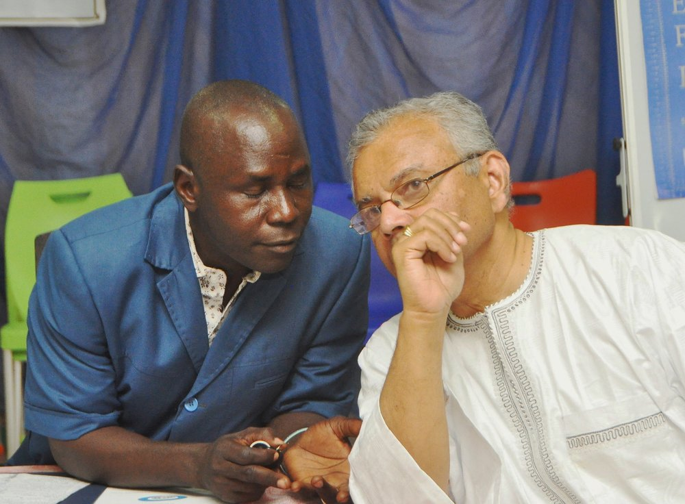 The Rev. Abare Kallah consults with OMNIA president Premawardhana.