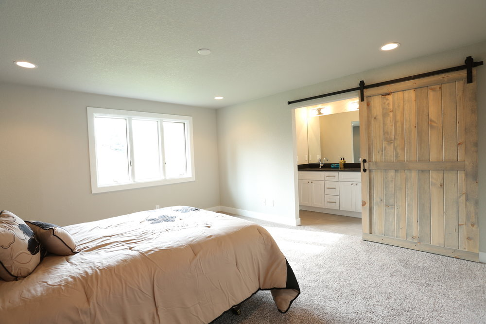 large master bedroom with custom barn door and his and her closets