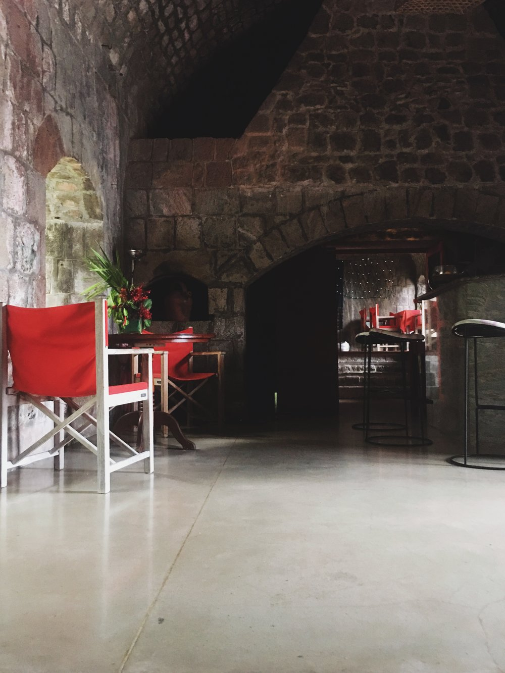 Centuries-old stone vaulted ceiling, smooth concrete floors and bold accent colors create an inviting atmosphere in the bar at Golden Rock Inn