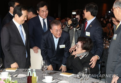 Former First Lady Lee Hee-ho, widow of late former President Kim Dae-jung, chats with Democratic Party presidential front-runner Moon Jae-in and others in a ceremony in Seoul on Dec. 8, 2016, to mark the 16th anniversary of her husband's Nobel Peace Prize. Kim was given the prize for holding the first-ever inter-Korean summit. (Yonhap)