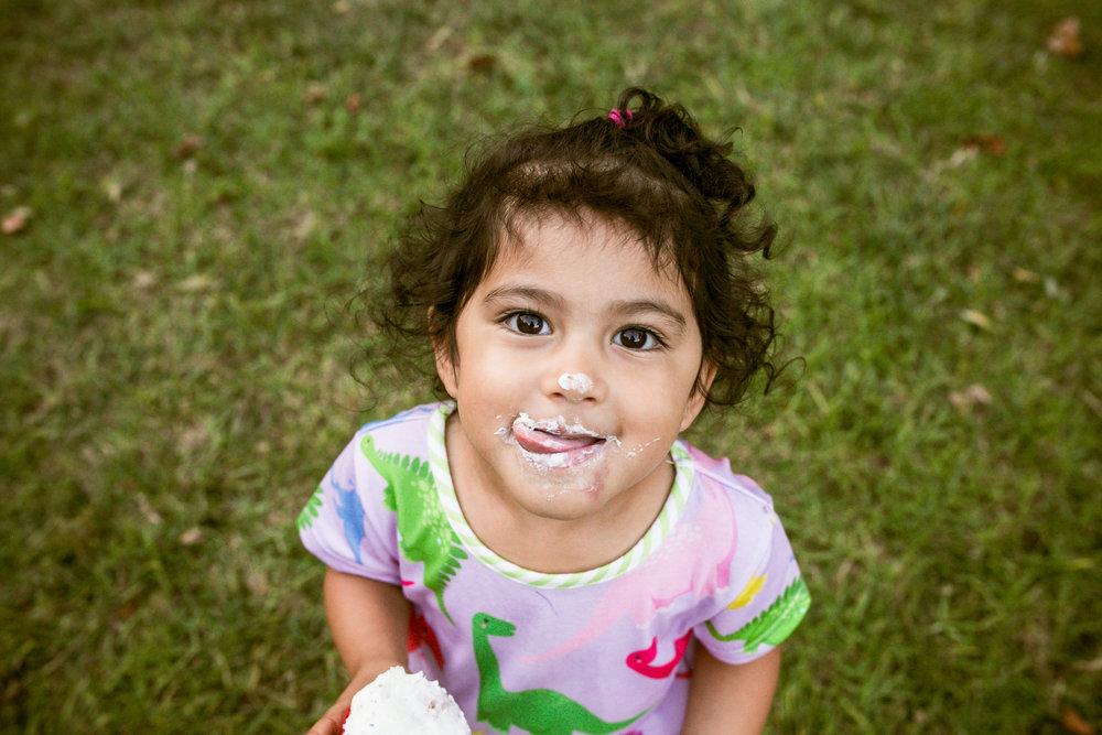 Little girl eating cupcake.