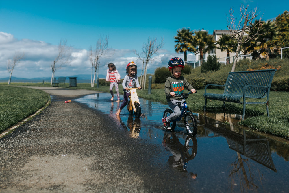 kids riding bikes on the puddle